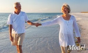 Older Couple Holding Hands as They Stroll on the Beach