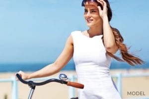 Woman in White Dress Holding Bicycle and Lifting her Sunglasses Up